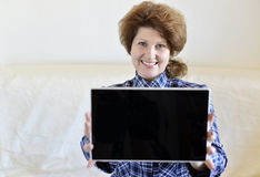 positive woman with a Tablet PC sitting on  sofa Royalty Free Stock Photography