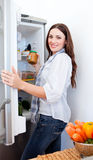 Positive woman taking something of the fridge. At home royalty free stock image