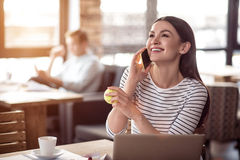 Positive woman talking on phone. Like communication. Overjoyed smiling beautiful women talking on cellphone and expressing gladness while her colleague sitting royalty free stock photo