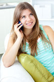 Positive woman talking on phone sitting on a sofa. At home Stock Photos
