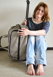 Positive woman with travel bag sitting by  wall. Positive woman with travel bag sitting by the wall Stock Photo