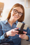 Positive woman using game console Stock Photography