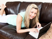 Positive woman using her laptop on the sofa Royalty Free Stock Image