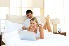 Positive woman using a laptop lying on bed Royalty Free Stock Photography