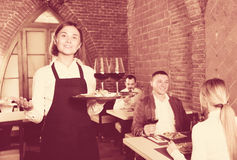 Positive woman waiter demonstrating restaurant to visitors Stock Photos