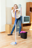 Positive  woman washing parquet floor with mop Stock Images