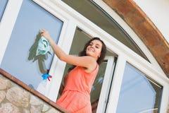 Positive woman washing plastic windows Stock Photo