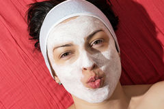Positive woman with white smoothing face mask sending kiss. Positive young woman with white smoothing face mask sending kiss Royalty Free Stock Image