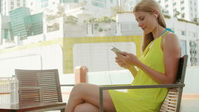 Positive woman in yellow dress sitting on chair near swimming pool listening to music on smartphone stock video footage