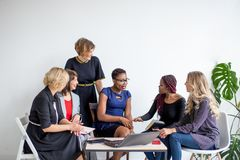 Positive women discuss organization plan while sitting at the table with laptop royalty free stock images