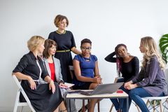 Positive women discuss organization plan while sitting at the table with laptop royalty free stock photo