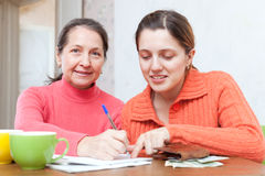 Positive women fills in utility payments bills. Two positive women fills in utility payments bills at  home Royalty Free Stock Images
