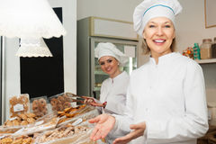 Positive women selling pastry. Positive women with hats selling pastry in shop stock photos