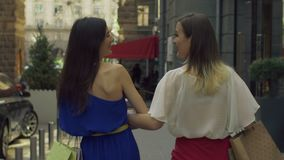 Positive women with shopping bags walking on street stock footage