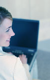 Positive worker. Young businesswoman works on laptop Stock Images