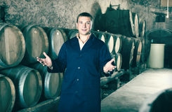 Positive worker posing with wine barrels Stock Photo