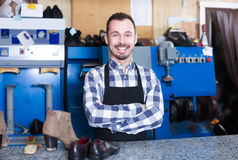 Positive worker showing his workplace and tools. Positive male worker showing his workplace and tools in shoe repair workshop Royalty Free Stock Photos