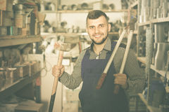 Positive working man showing various tools. At workshop Stock Photography