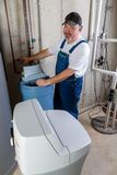 Workman installing a household water softener. Positive workman installing a replacement household water softener smiling at the camera as he works on the new Stock Photography