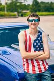 Positive young American guy standing at his car. Portrait of positive young American guy standing at his car with folded arms, looking at camera and smiling Stock Image