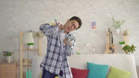 Positive young Asian man with glasses in the living room of the house throws banknotes. Close up stock video