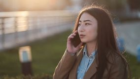 Positive young asian woman talking on mobile phone stock footage
