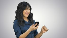 Positive young beautiful asian woman using mobile phone, dancing and smiling on white background stock photo