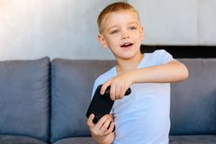 Positive young boy playing video games. Modern entertainment. Positive cute young boy holding a game console and playing video games while sitting on the sofa Stock Photo