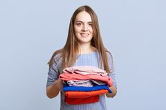 Positive young brunette female holds pile of laundry, being tired after ironing, has happy expression, isolated over light blue ba Royalty Free Stock Photo