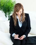 Positive young businesswoman taking notes at home. Positive young businesswoman taking notes sitting on a sofa Stock Image