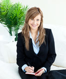 Positive young businesswoman taking notes smiling. At the camera sitting on a sofa Royalty Free Stock Image