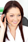 Positive young businesswoman wearing earpiece Royalty Free Stock Photography