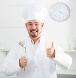Positive young cook holding soup ladle Royalty Free Stock Photo
