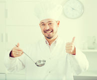 Positive young cook holding soup ladle Stock Image