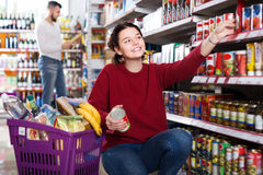 Positive young couple choosing purchasing canned food for week a. Positive young couple choosing ordinary family purchasing canned food for week at supermarket Royalty Free Stock Images