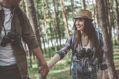 Positive young couple in love is walking in forest royalty free stock images