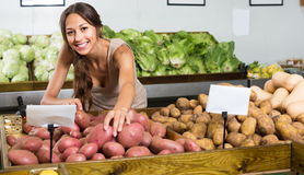 Positive young female customer taking potatoes Stock Photography