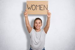 Positive young female dressed in casual t shirt, holds plate with inscription Women, has glad facial expression, being feminist, i. Solated over white background royalty free stock photography