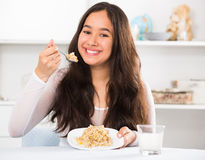 Positive young female eating cereals stock photos