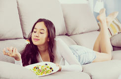 Positive young female eating salad Royalty Free Stock Photos