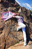 Positive young girl against the rock in summer Stock Images