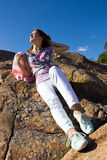 Positive young girl against the rock in summer Royalty Free Stock Images