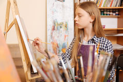 Positive young girl practicing painting in the art school Royalty Free Stock Images