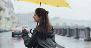 Girl rejoices rain walking along the embankment. Positive young girl rejoices the spring rain walking along the embankment under an umbrella enjoying cloudy stock video footage