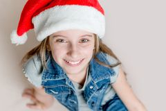 Positive young girl in santa claus hat royalty free stock photo