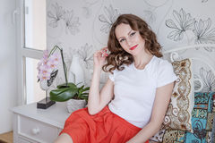 Positive young girl smiles in her bedroom. Positive young girl smiles in her white bedroom in orange skirt Royalty Free Stock Image