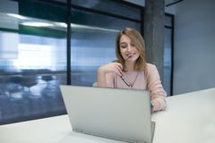 Positive young girl working at a laptop in the office and smiling. Work in coworking royalty free stock image