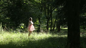 Positive young happy girl dancing and having fun in beautiful dress at green summer forest glade slow-motion stock video footage