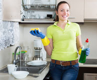 Positive young housewife washing dishes Royalty Free Stock Photo