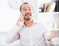 Positive young man calling by smartphone. Portrait of smiling young worker with his smartphone in office Royalty Free Stock Image